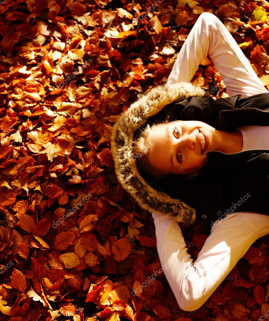 Portrait of beautiful young female lying over a bed of dried leaves — Stock Photo #3294772