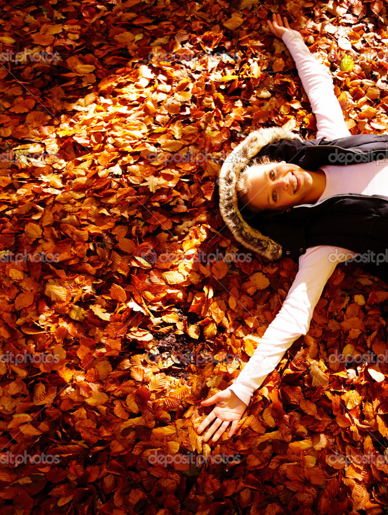 Portrait of beautiful young female lying over a bed of dried leaves with her arms spread  Stock Photo #3294775