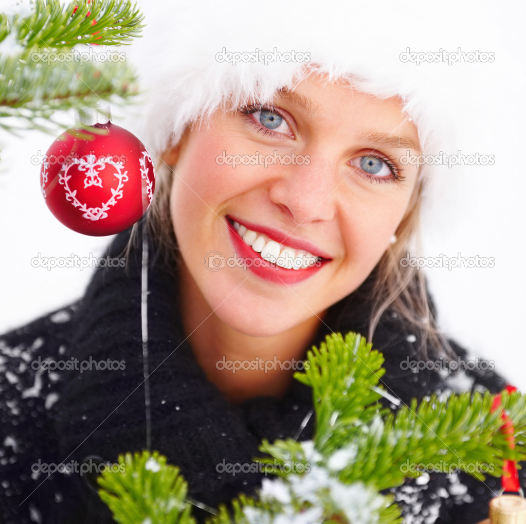 Girl in winter cap by a Christmas tree over white background — Stock Photo #3294799