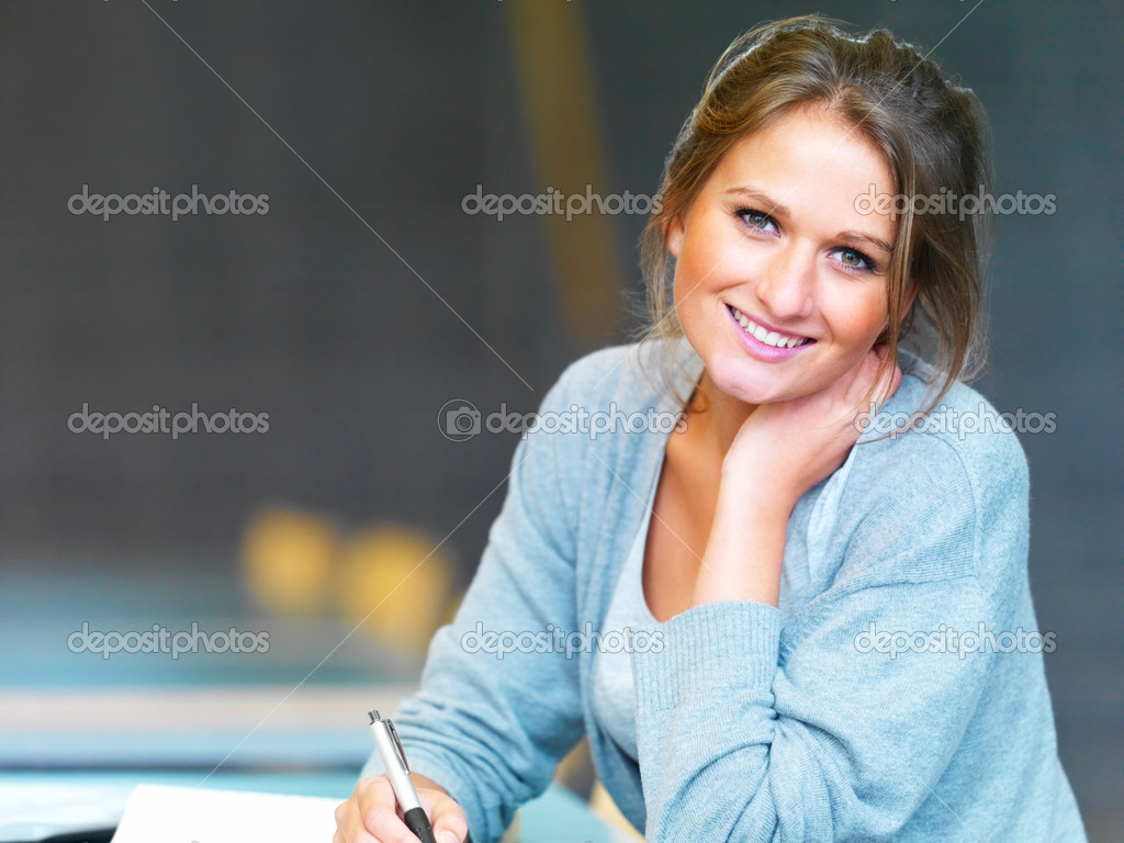 Closeup of a young happy woman writing notes — Stock Photo #3294978