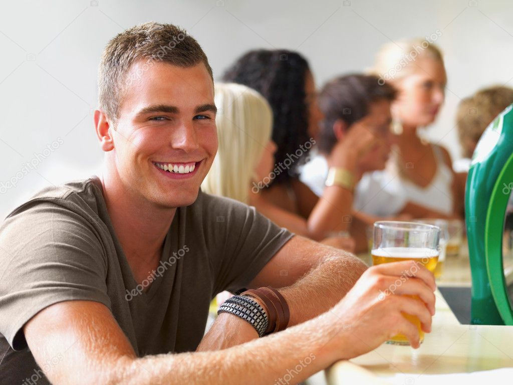 Happy young boy holding a glass of beer at a disco — Stock Photo #3296149