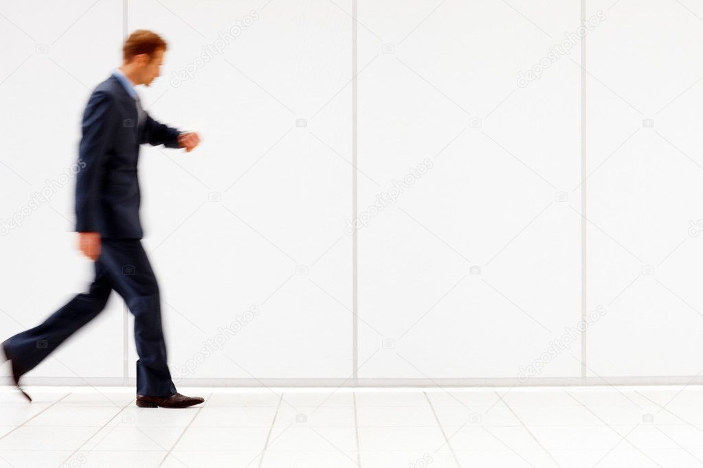 Blurred image of a young business man checking time and walking over white background  Stock Photo #3296521