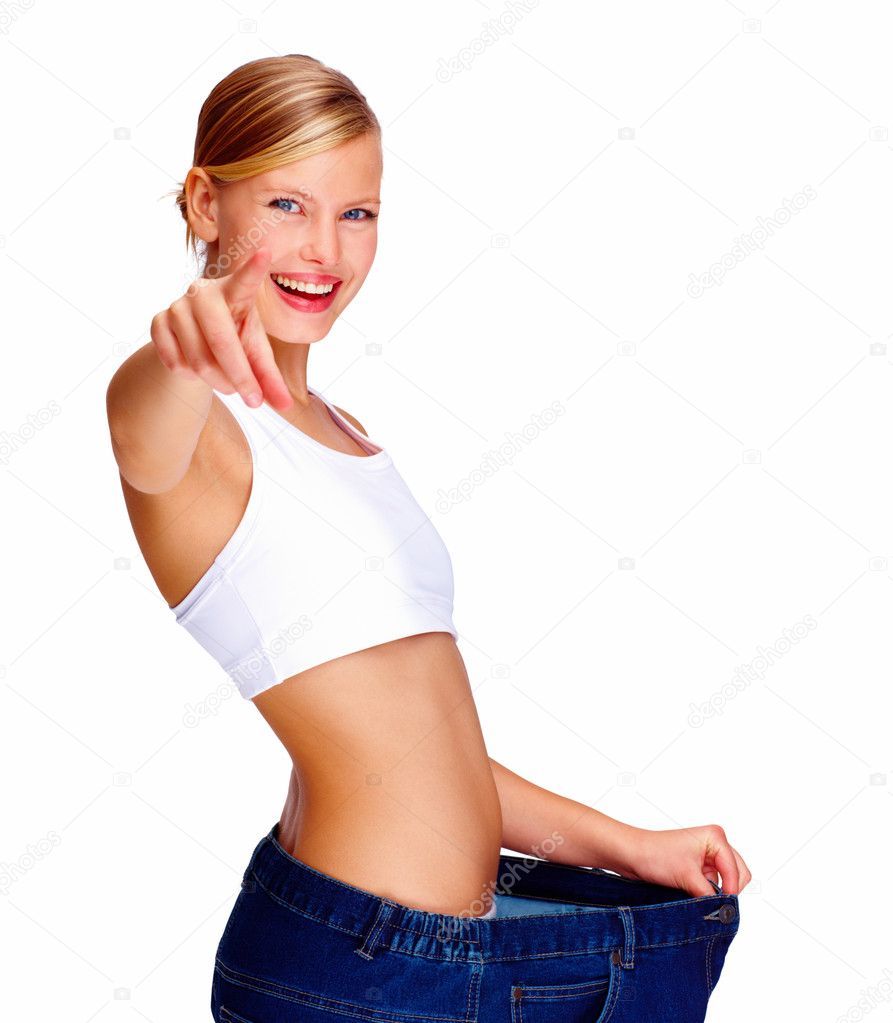 Happy young woman in old jeans pant after losing weight and pointing towards the camera  Stock Photo #3297898