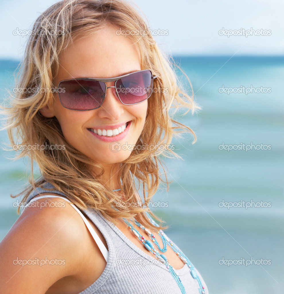 Beautiful woman wearing goggles and smiling at the beach  Stock Photo #3299223