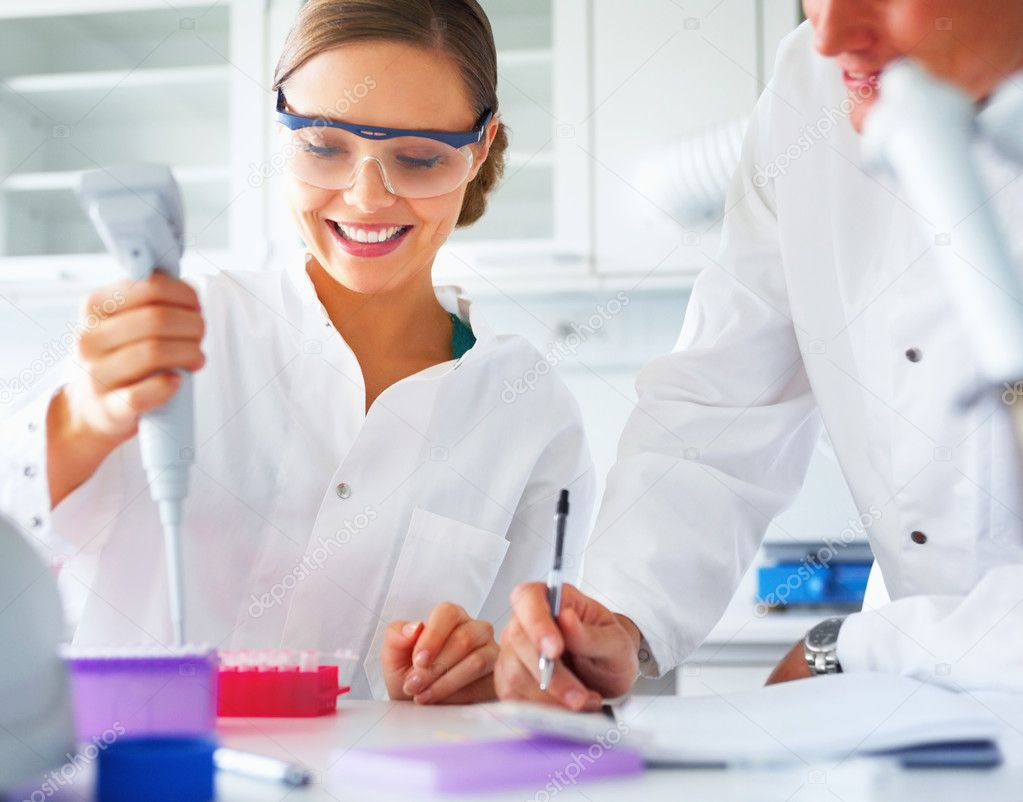 Happy scientists analyzing together in a laboratory  Stock Photo #3299385