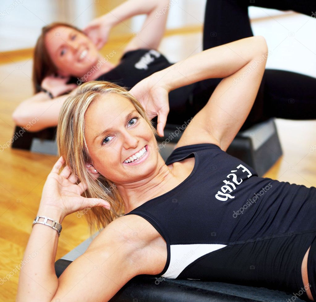 Young pretty women exercising in a fitness center — Stock Photo #3299456