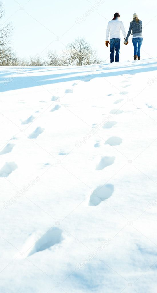 Rear view image of a young couple walking on snow and leaving a trail behind  Stock Photo #3299987