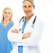 Royalty-Free Stock Photo: Happy doctor with hands folded and a colleague at the back on wh