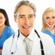 Royalty-Free Stock Photo: Closeup of a happy old doctor with female colleagues at the back