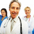 Confident doctor with other colleagues at the back - Stock Photo
