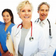 Confident female doctor with other colleagues at the back - Stock Photo