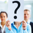 Closeup of businesspeople holding question mark on boards - Stok fotoğraf