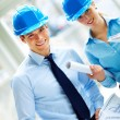 Portrait of contracters in blue helmet with blueprints - Stock Photo