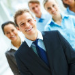 Young business man with other colleagues at the back - Stock Photo