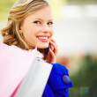 Royalty-Free Stock Photo: Cute young woman holding shopping bags and speaking an a mobile