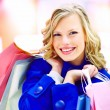 An excited pretty woman holding many shopping bags - Stok fotoğraf