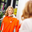 Young woman holding an orange full sleeve dhirt and looking at h - Stock Photo