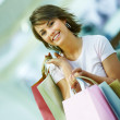 Portrait of a beautiful young woman holding shopping bags - Стоковая фотография