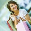 Portrait of a attractive young woman holding shopping bags - Стоковая фотография