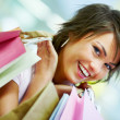 Portrait of a cute young woman holding shopping bags - Stock Photo