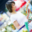 Pretty young woman purchasing grocery at the store - Stock Photo