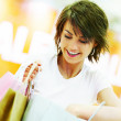 Happy young woman checking through her shopping bags - Lizenzfreies Foto