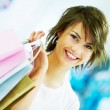 Happy young woman holding a shopping bags at a store - Stock Photo