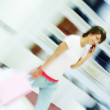 Blur motion image of a happy female carrying shopping bags while - Stok fotoğraf