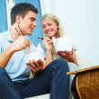 Young couple eating from a takeaway container with chopsticks - Stock Photo