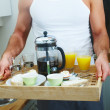 Cut image of a man holding a breakfast tray - Stock Photo