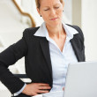 Royalty-Free Stock Photo: Business woman sitting in the office with pain in lower back
