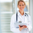 Royalty-Free Stock Photo: Happy successful mature female doctor holding a writing pad