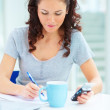 Young female sitting with coffee cup making notes and using mobi - Stock Photo