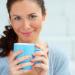 Closeup portrait of happy young female holding a coffee cup - Stock Photo