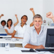 Excited business colleagues at work with their hands raised - Stock Photo