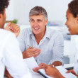 A consultant discussing with colleagues at work - Stock Photo