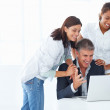 Royalty-Free Stock Photo: Team of cheerful business colleagues working together on a lapto