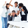 Team of happy business working together on a laptop - Stock Photo