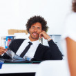 Happy young business man relaxing at work - Stock Photo