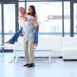 Royalty-Free Stock Photo: Smart male piggybacking her wife in the living room
