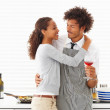 Man holding a glass of wine in the kitchen with his wife hugging - Stock Photo