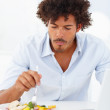 Happy young man having a meal while on a laptop - Stock Photo