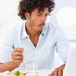 Handsome young business man having a meal while on a laptop - Stock Photo