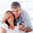 Royalty-Free Stock Photo: Mature man covering his wife\'s eyes to surprise her with a ring