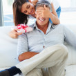 Royalty-Free Stock Photo: Woman covering her husband\'s eyes to surprise him with a gift