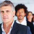 Royalty-Free Stock Photo: Confident happy businessman standing in a line with his business
