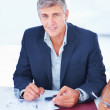 Royalty-Free Stock Photo: Handsome successful mature business man sitting on a desk