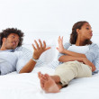 Portrait of a young African American couple lying on the bed and - Stock Photo