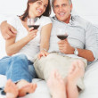 Royalty-Free Stock Photo: Cute mature couple lying on their bed enjoying a glass of wine