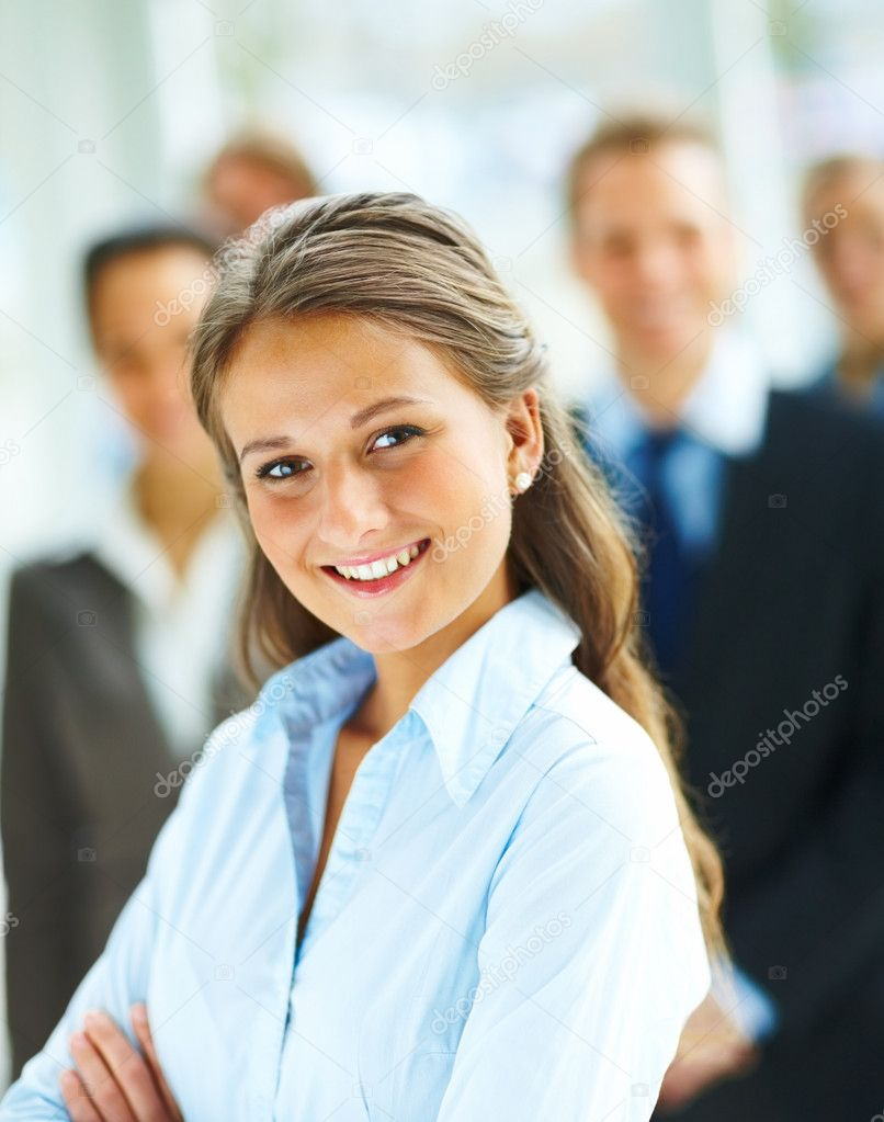 Portrait of a cute business woman with her hands folded and other colleagues at the back — Stock Photo #3300452
